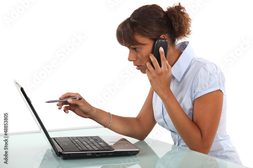 Woman on the phone in front of computer