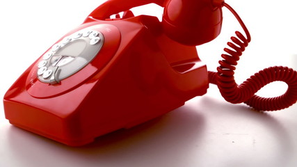 Receiver falling on red dial phone in slow motion