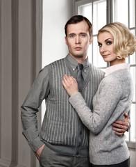 Elegant couple indoors standing near window