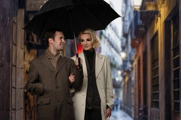 Elegant couple with umbrella walking outdoors in the rain