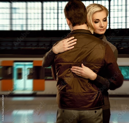 Beautiful couple embracing on train station - 48854284