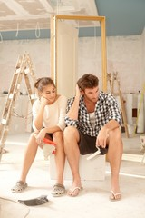 Exhausted couple in renovating home