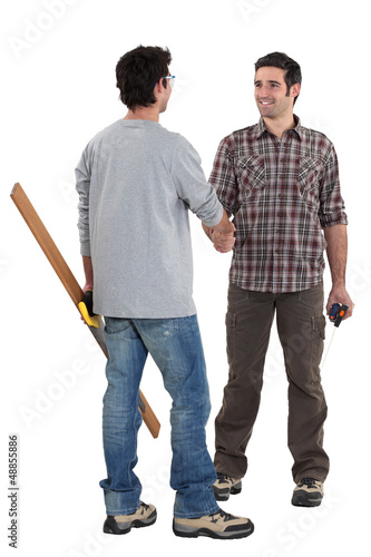 Two carpenters shaking hands