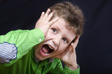 Young emotional kid on dark fabric background