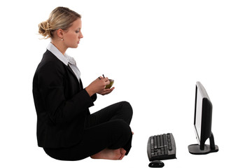 Blond businesswoman sat cross-legged in front of laptop