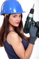craftswoman holding electric drill
