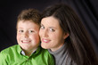 Mother and son on dark fabric background