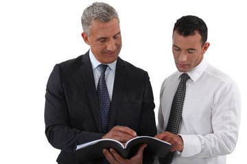Two businessmen reading document