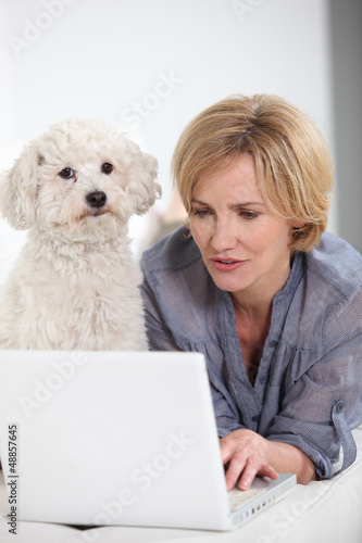 Woman on laptop computer accompanied by small white dog
