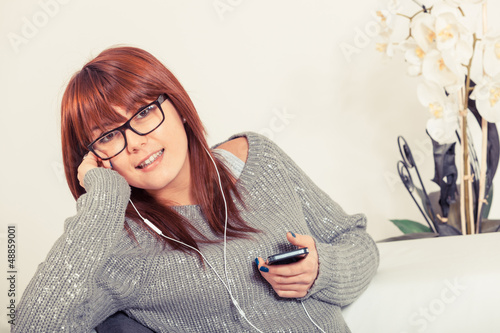 Beautiful Young Woman Listening Music on the Sofa