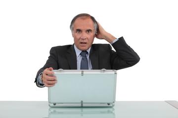 Shocked man looking in an aluminium briefcase