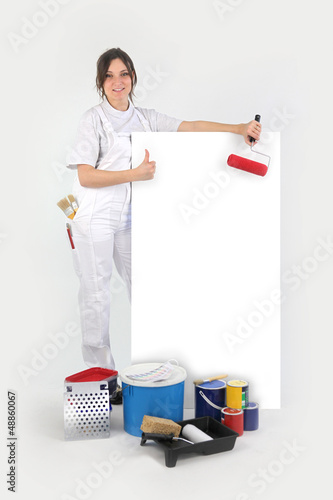 Painter posing with her supplies next to a blank sign