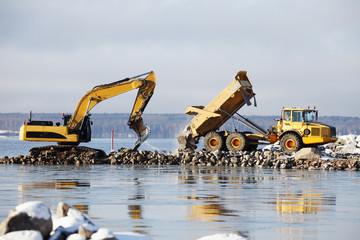 bulldozer dredging in the sea, truck delivering rocks