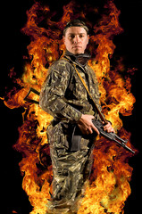 A soldier stands with a gun in a burning fire