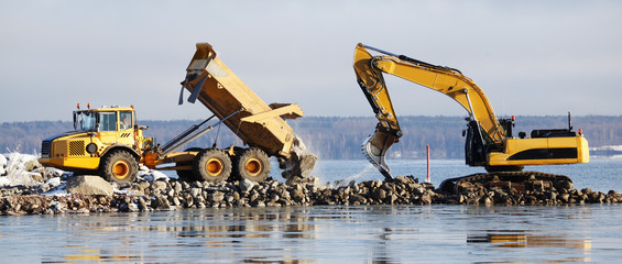 bulldozer dredging with truck delivering rocks