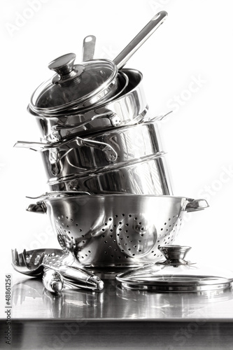 Stack with stainless steel pots and pans on white