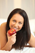 Naked woman eating an apple in bed