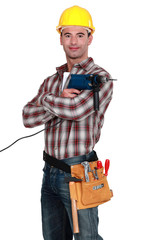 Proud tradesman posing with his electric screwdriver