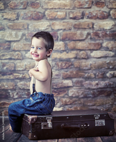 Small kid playing on the suitcase