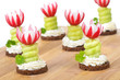 Dekorative Käsehäppchen mit Gurke und Radieschenblüte