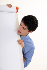 A businessman looking at a blank board.