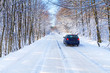 Snowy road in winter forest with single car of Poland