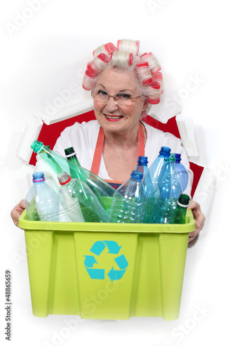 granny with hair curlers holding recycling tub