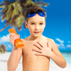 boy applying sun block cream on the tanned body