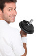 Smiling man looking over his shoulder holding dumbbell