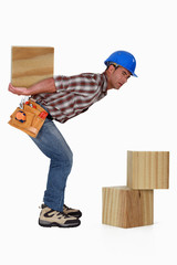 Handyman carrying wooden blocks on his back