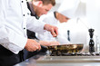 Three chefs in team in hotel or restaurant kitchen - 48867206