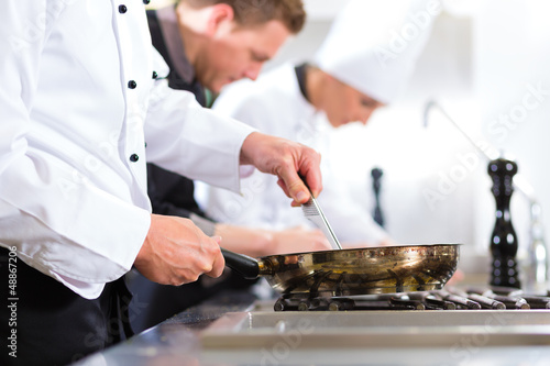 Three chefs in team in hotel or restaurant kitchen