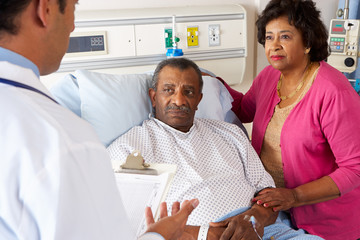 Doctor Talking To Senior Couple On Ward