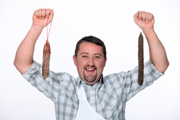 Man holding cured sausages