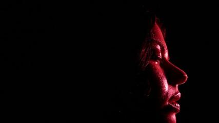 volto di ragazza che dorme e sogna nell'oscurità con luce rossa