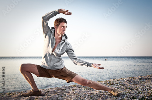 Young attractive man making Thai-chi movements