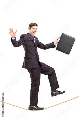 Young businessman with briefcase walking on a rope