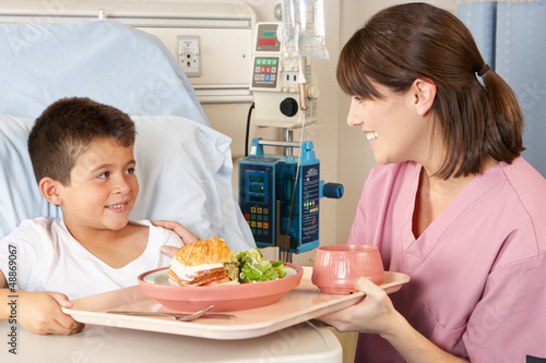 Nurse Serving Child Patient Meal In Hospital Bed