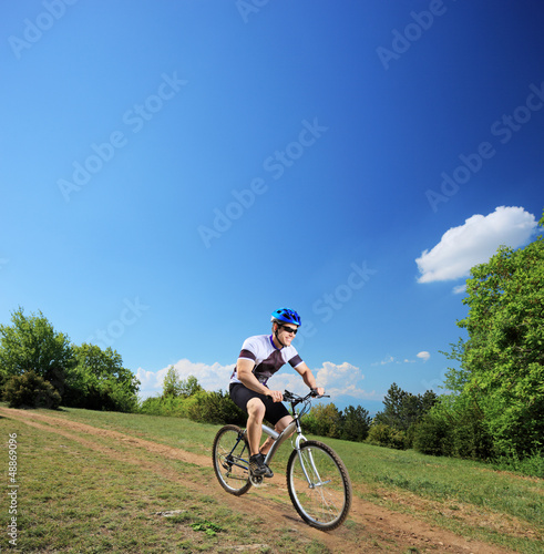 Male bicyclist riding a mountain bike downhill
