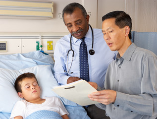 Doctors Visiting Child Patient On Ward