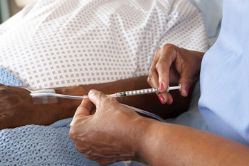 Nurse Injecting Senior Male Patient In Hospital Bed