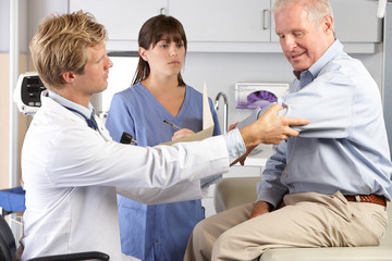 Doctor Examining Male Patient With Elbow Pain