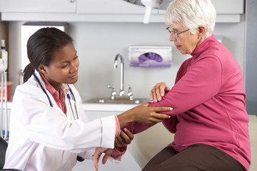 Doctor Examining Female Patient With Elbow Pain