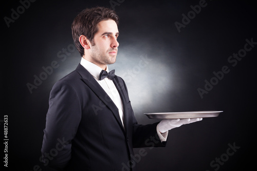 Portrait of a young waiter holding an empty dish on black backgr