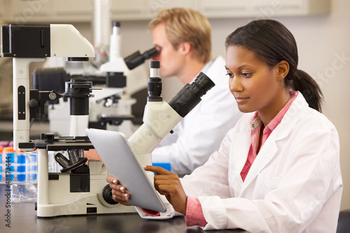Scientists Using Microscopes  And Digital Tablet In Laboratory
