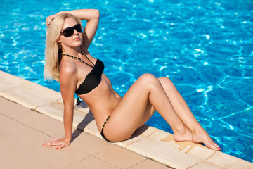 beautiful blonde model posing by the pool