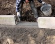 Construction site - Worker laying concrete curbs