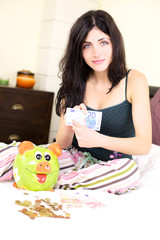 Woman holding money with piggybank happy