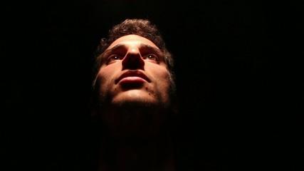 luce riflessa su volto maschile e sfondo nero