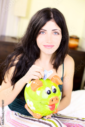 Happy woman putting money in piggy bank